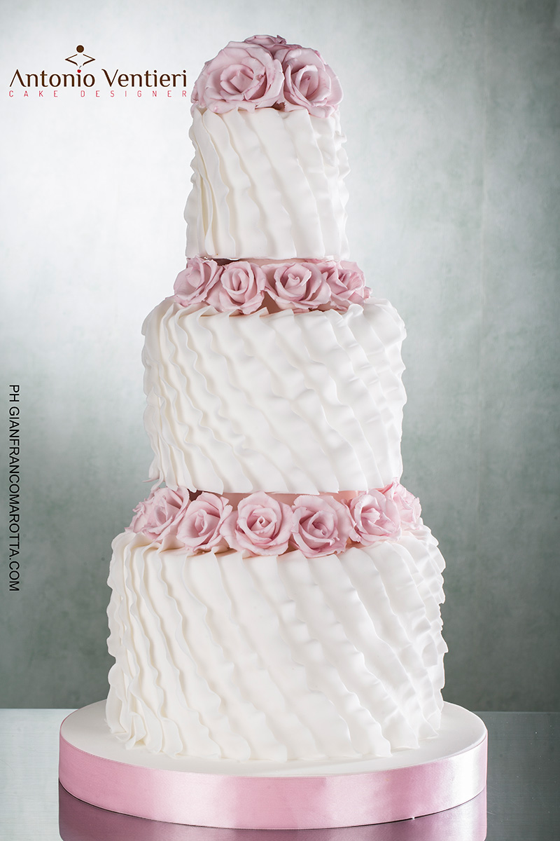 White wedding cake with pink sugar roses
