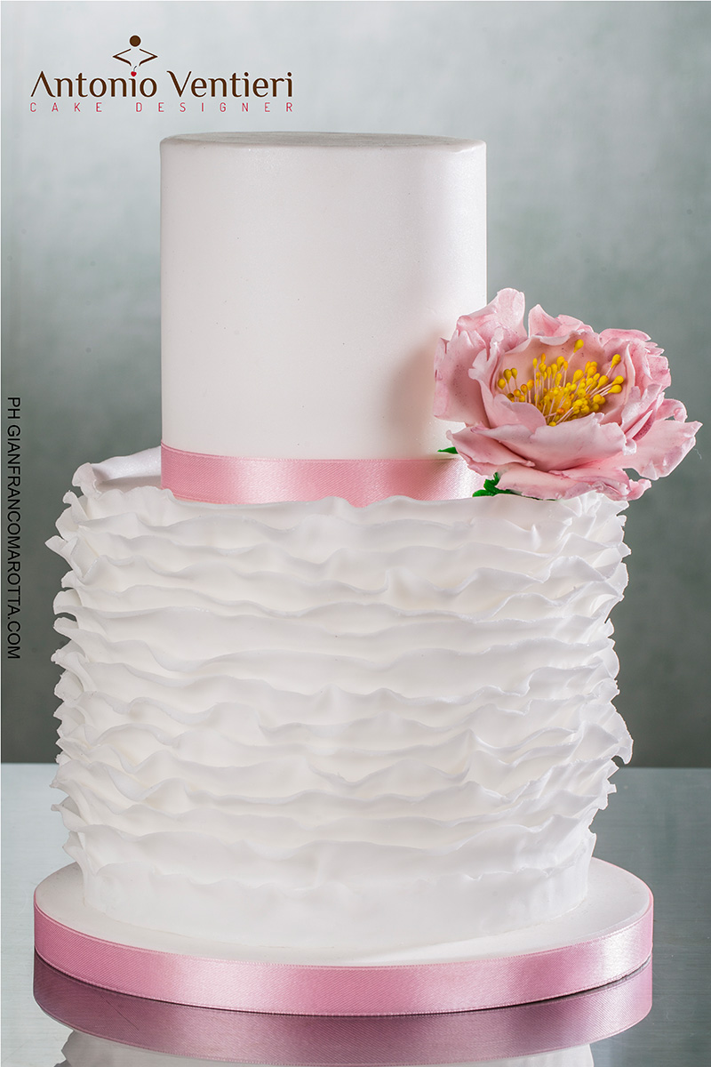 White ruffle wedding cake with pink sugar flower