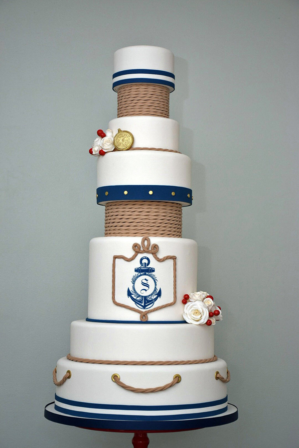 Tall white fondant nautical cake with blue detailing
