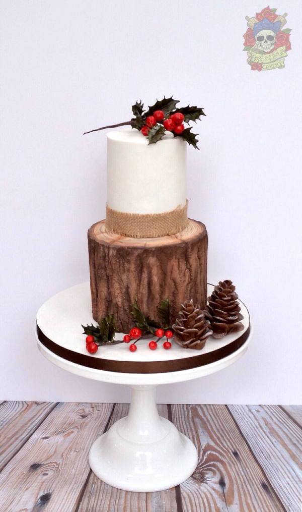 White fondant cake with exposed bark and pinecones