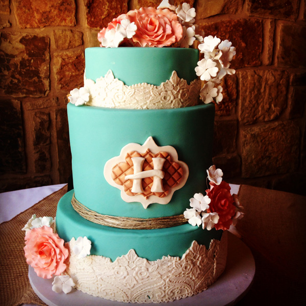 Turquoise fondant wedding cake with white lace overlay and coral sugar flowers