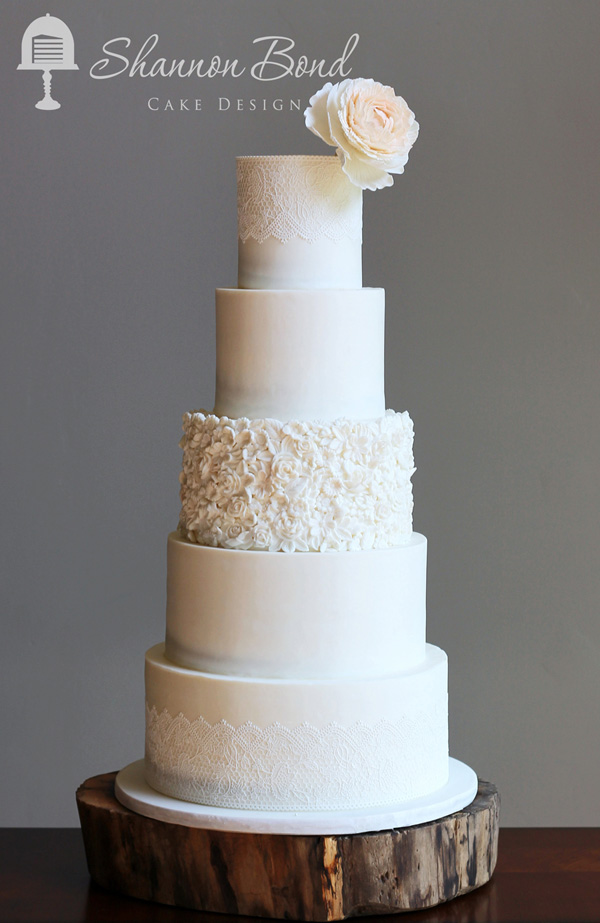 All white fondant wedding cake with ruffles and lace