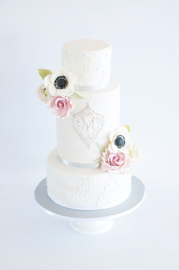 White tiered fondant wedding cake with anemone sugar flowers
