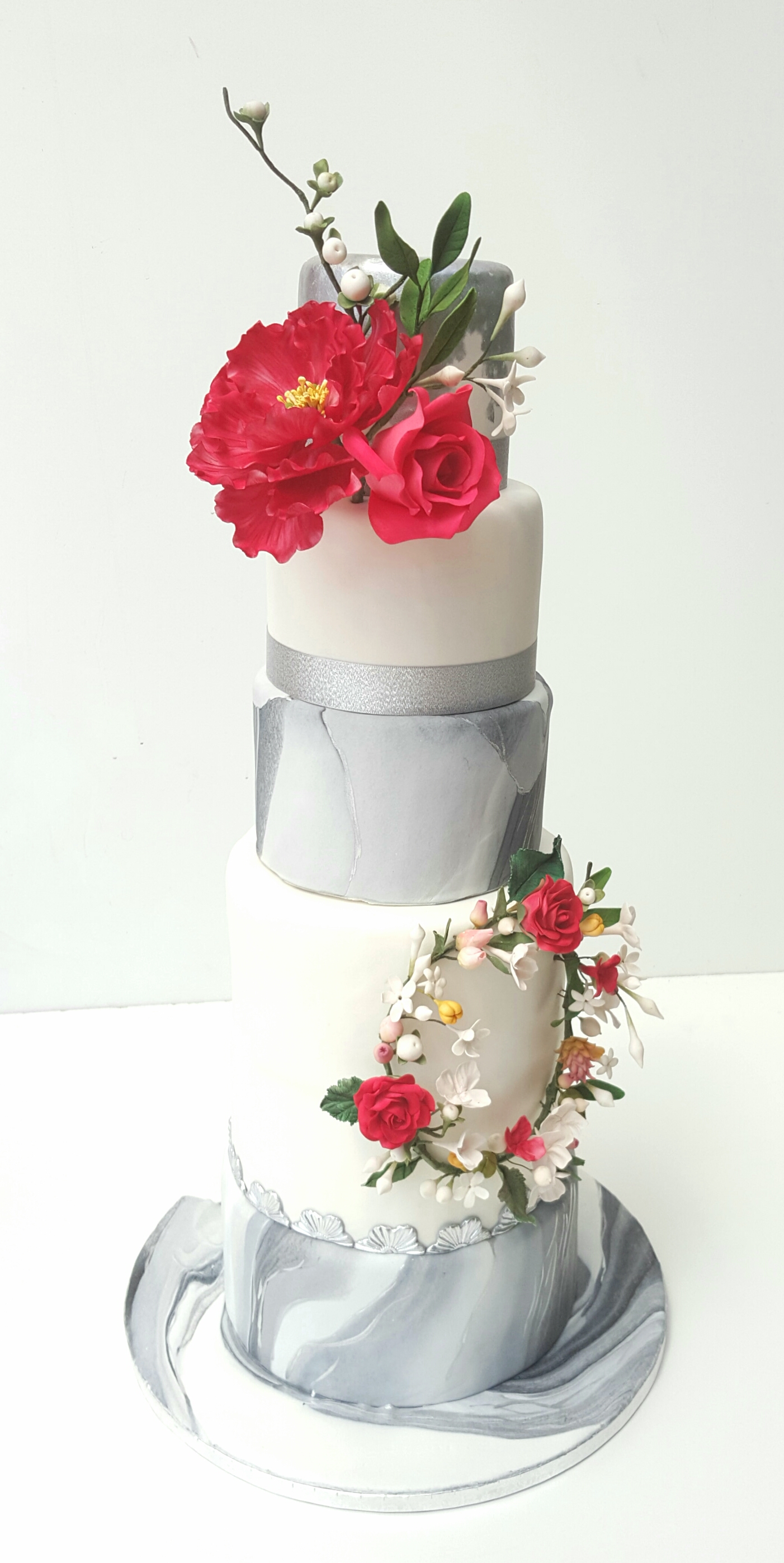 Gray and white marble wedding cake with red sugar flowers