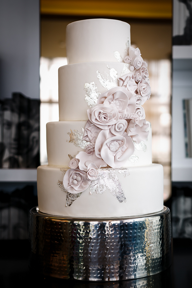 White wedding cake with light pink sugar flowers