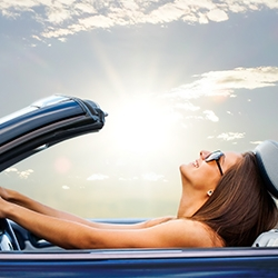 2018 07 02 Blog Reviewingcoverage Newcar Teaser Woman Driving Convertible Smiling Sunshine