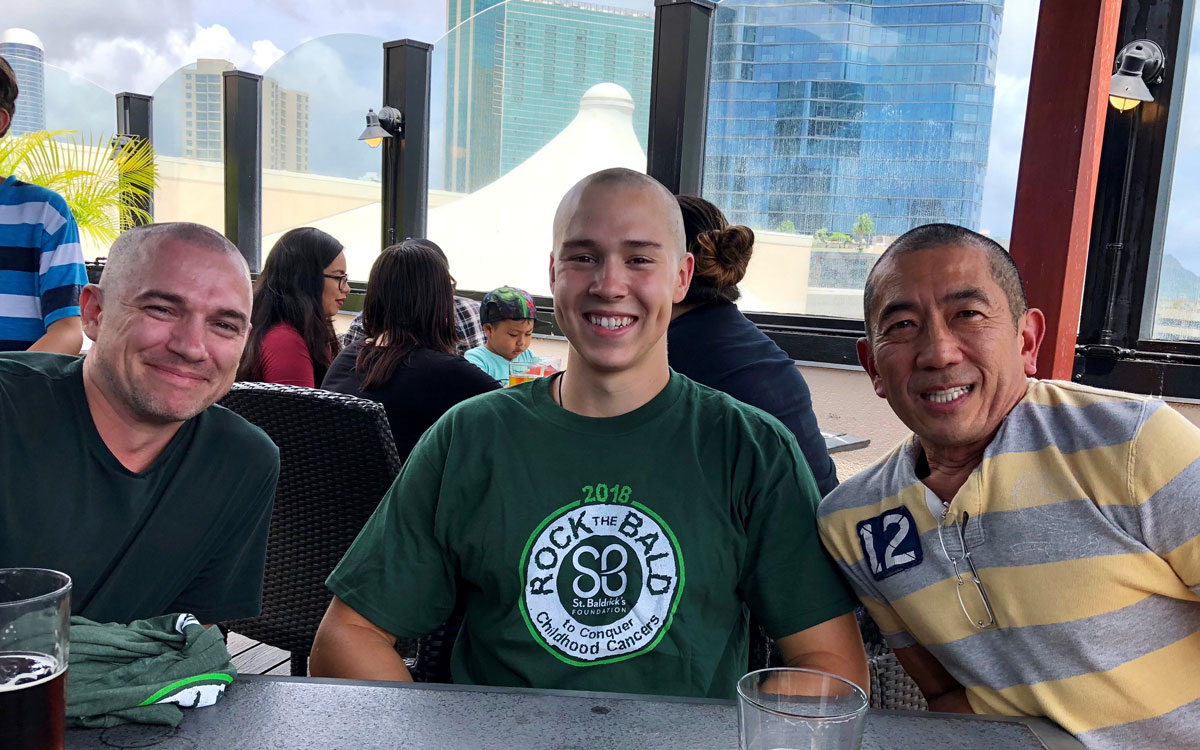 Dr. Bruce Shiramizu appears with two colleagues after shaving his head to raise money for childhood cancer research.
