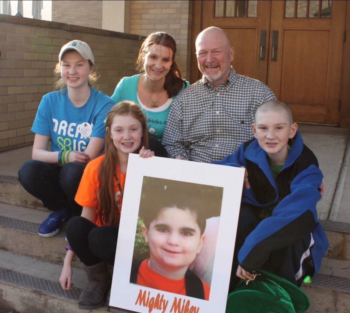 John Bender appears with members of his family in 2009. They're holding a photo of Mighty Mikey, who died after being diagnosed with brain and spinal tumors.