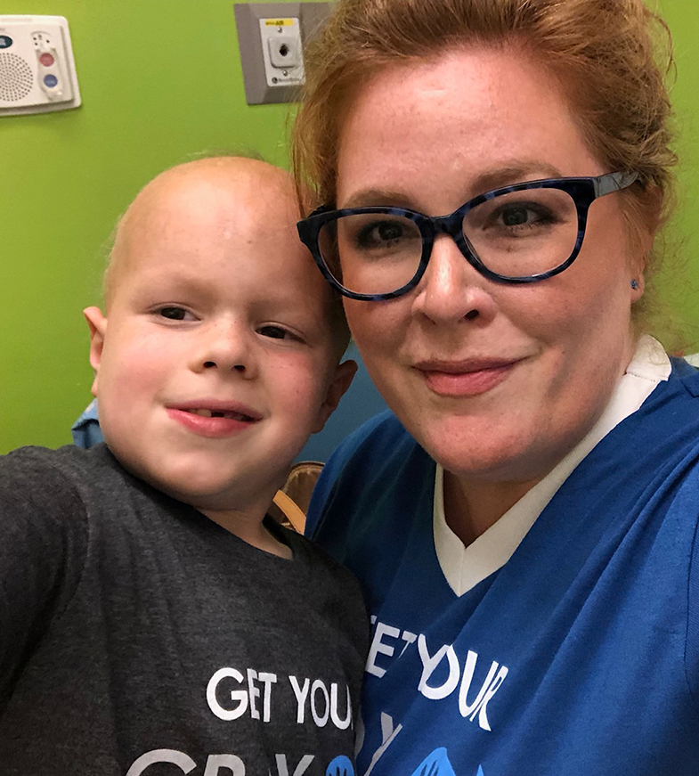 Ellie and her child, who has pediatric cancer, take a selfie in the hospital.