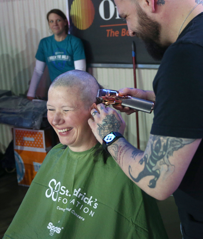 Dr. Jamie Renbarger is having her head shaved by a barber at a St. Baldrick's head-shaving event.