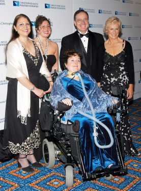 Brooke Ellison, shown above center, with her family at a Reeve Foundation gala in 2004, allowed researchers to test a mobile solar generator at her home for six months (PHOTO CREDIT : MCT CAMPUS)
