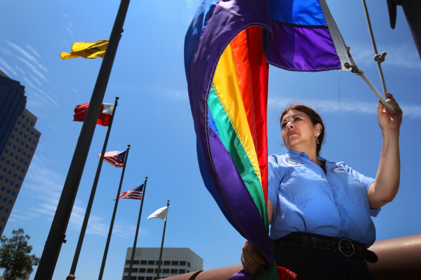 City maintenance worker Maria Burgos holds a Rainbow Pride Flag ahead of it's raising by Long Beach Mayor Robert Garcia, the city's first openly gay mayor, over the Civic Plaza in response to a U.S. Supreme Court ruling legalizing same-sex marriage on Friday, June 26, 2015. (Rick Loomis/Los Angeles Times/TNS)
