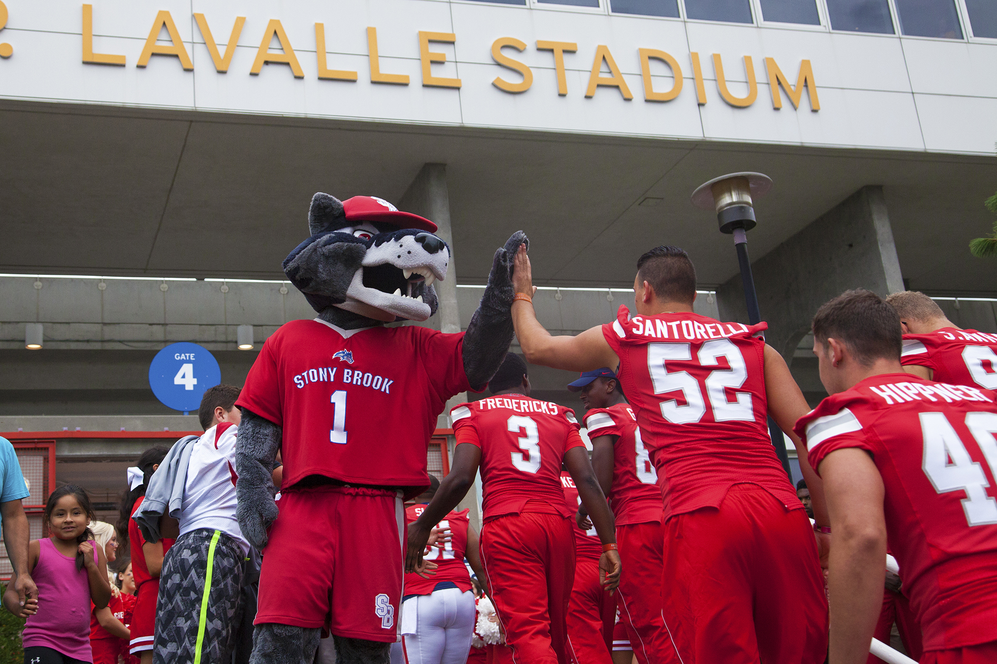 Wolfie high-fiving the Stony Brook Seawolves as they enter Kenneth P. LaValle stadium for their match against Central Connecticut. GISELLE MIRANDA/THE STATESMAN