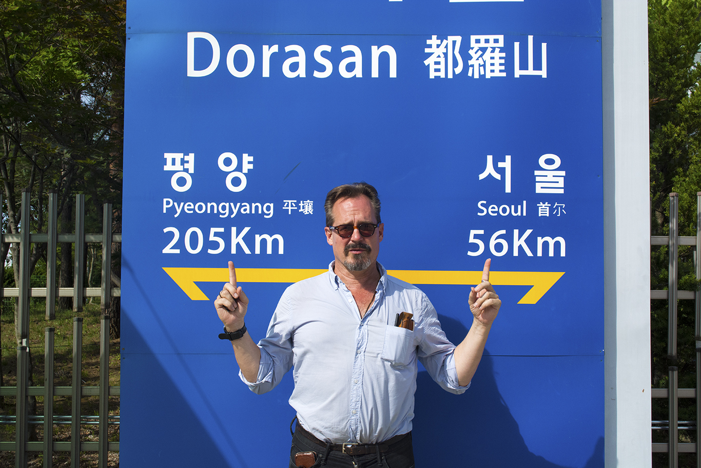 Professor Philip Baldwin from the Department of Theatre Arts at Stony Brook University poses in front of a sign at Dorasan Station on the South Korean side of the Military Demarcation Line. (CHRISTOPHER CAMERON/THE STATESMAN)