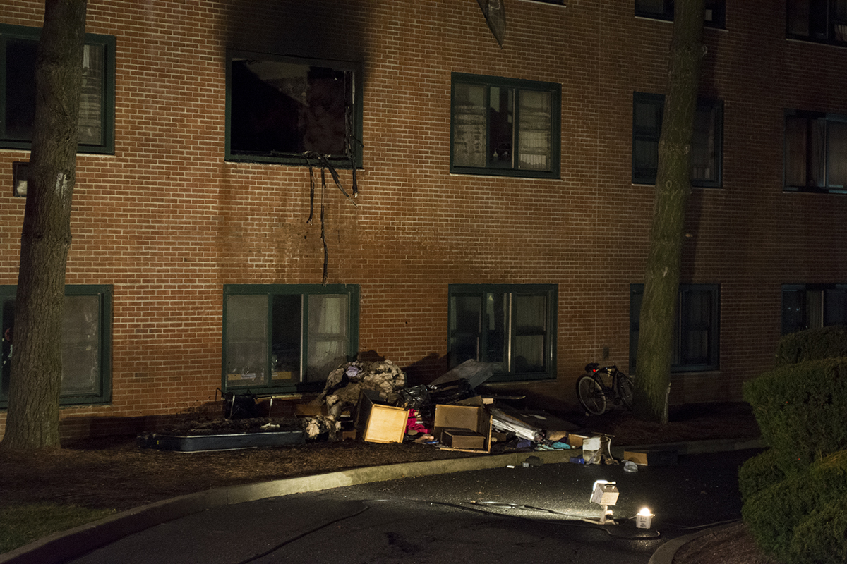 A fire broke out in an O'Neill College E wing dorm room (above, top left) on Nov. 21, 2015. The Setauket Fire Department responded and extinguished the fire before throwing the destroyed contents of the room out onto the lawn below. CHRISTOPHER CAMERON/THE STATESMAN
