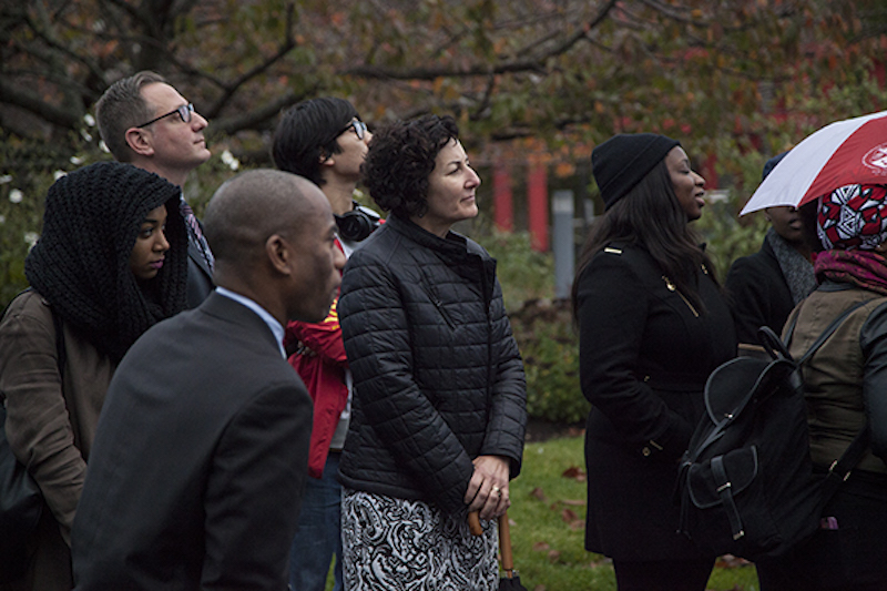 Judith Greiman, Chief Deputy to the President and Principal Officer for Government and Community Relations, watches as Stony Brook students take part in the demonstration. KELLY ZEGERS/THE STATESMAN [CORRECTION (NOV. 18, 2015): A PREVIOUS VERSION OF THIS CAPTION ERRONEOUSLY STATED THAT JUDITH GREIMAN IS THE ADVISER FOR THE STUDENT AFRICAN AMERICAN BROTHERHOOD AND THE CARIBBEAN STUDENT ORGANIZATION.]