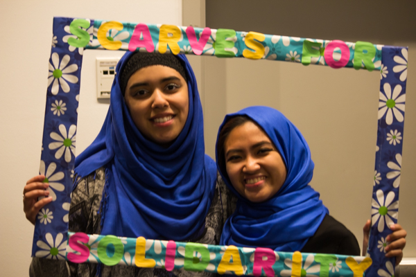 Sara Rahman, a junior health science major, poses with her friend Jennifer Celebrados, a junior health science major, holding the Scarves for Solidarity frame to show their participation. TIBIAN AHMED/THE STATESMAN