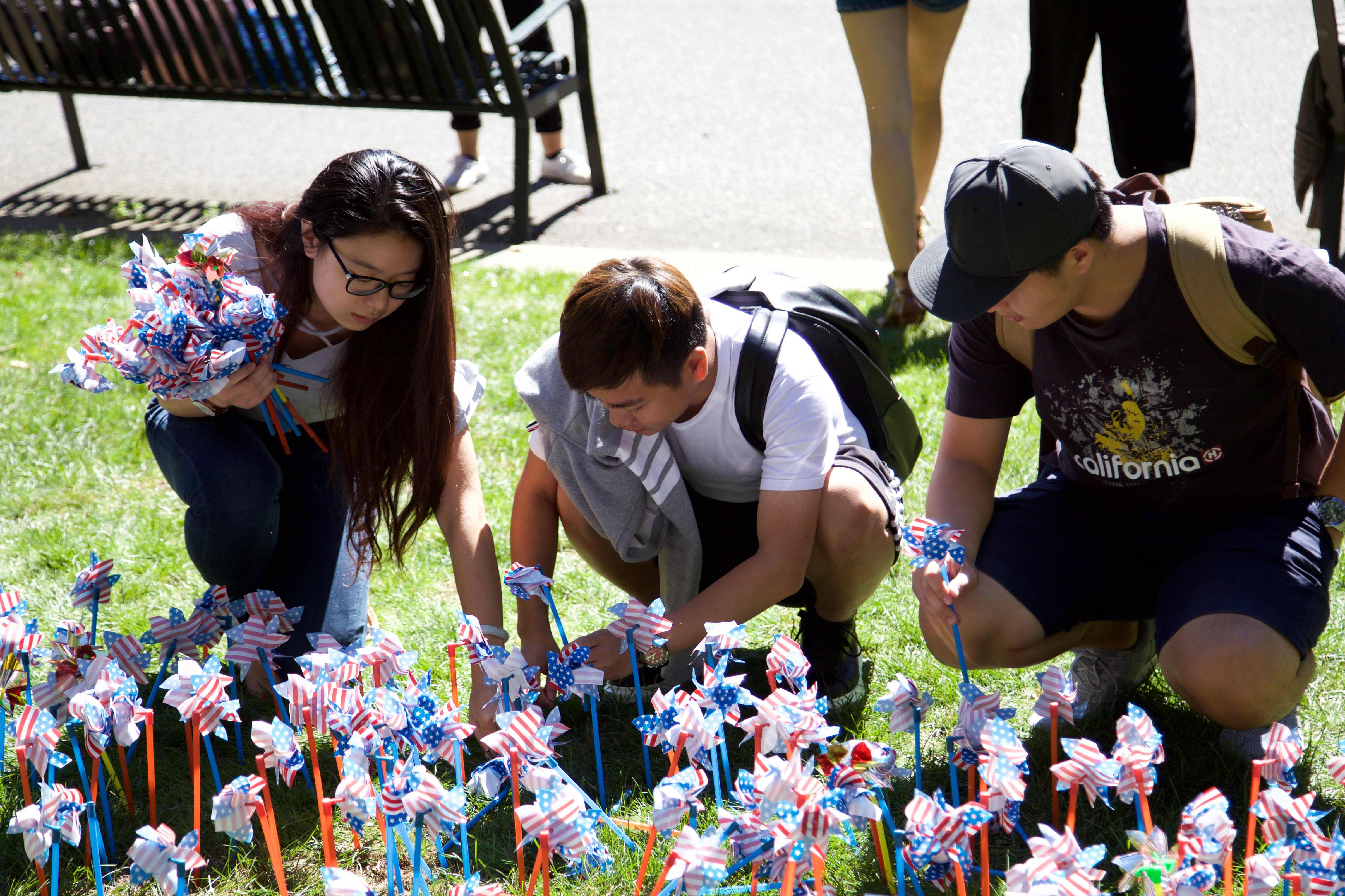 Students place commemorative pinwheels into the grass to remember 9/11. ANGELICA CARPENTER/THE STATESMAN