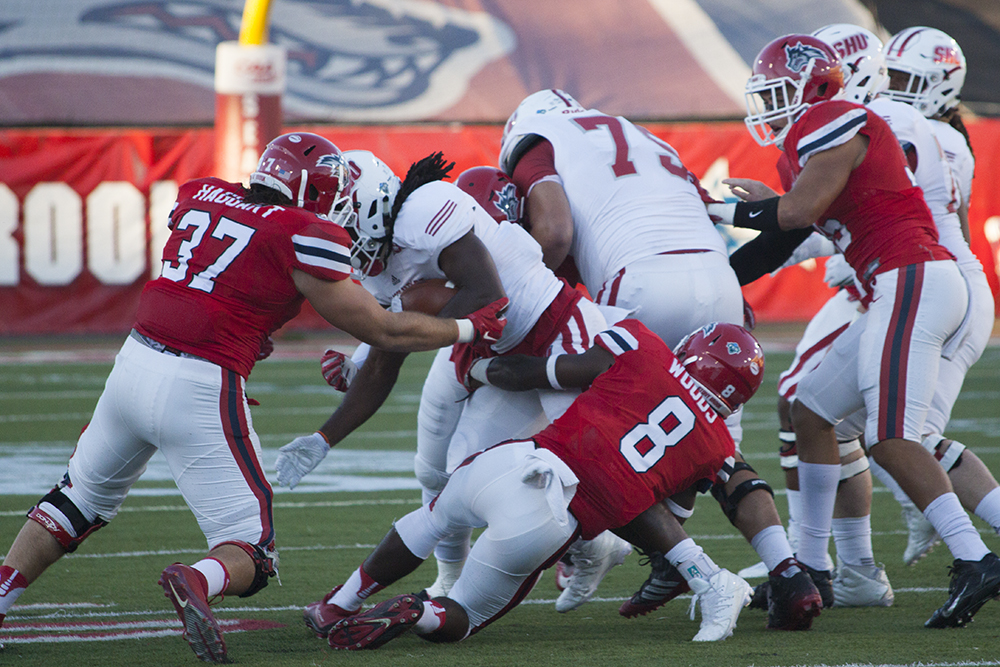 Junior linebacker John Haggart (No. 37) and Senior defensive back Jaheem Woods (No. 8) team up to make a tackle in a game against Sacred Heart University on Sept. 24, 2016. The defensive coach for the team, ARACELY JIMENEZ/THE STATESMAN