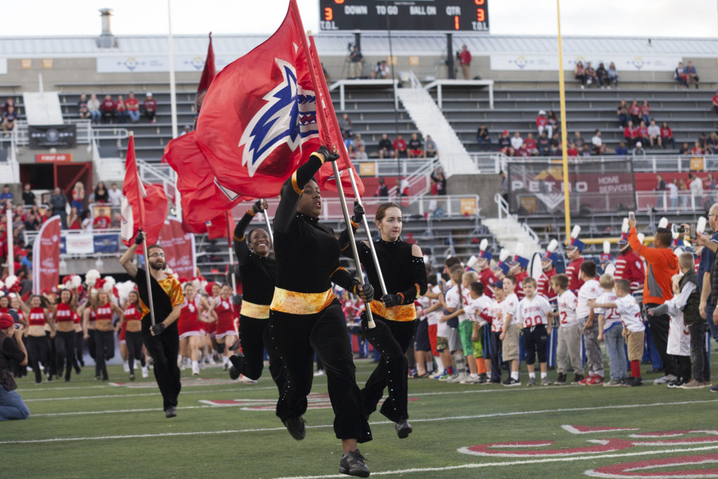 The color guard leads the charge with the Stony Brook Cheerleading Team, Dance Team and football team just before kickoff. ARACELY JIMENEZ/THE STATESMAN