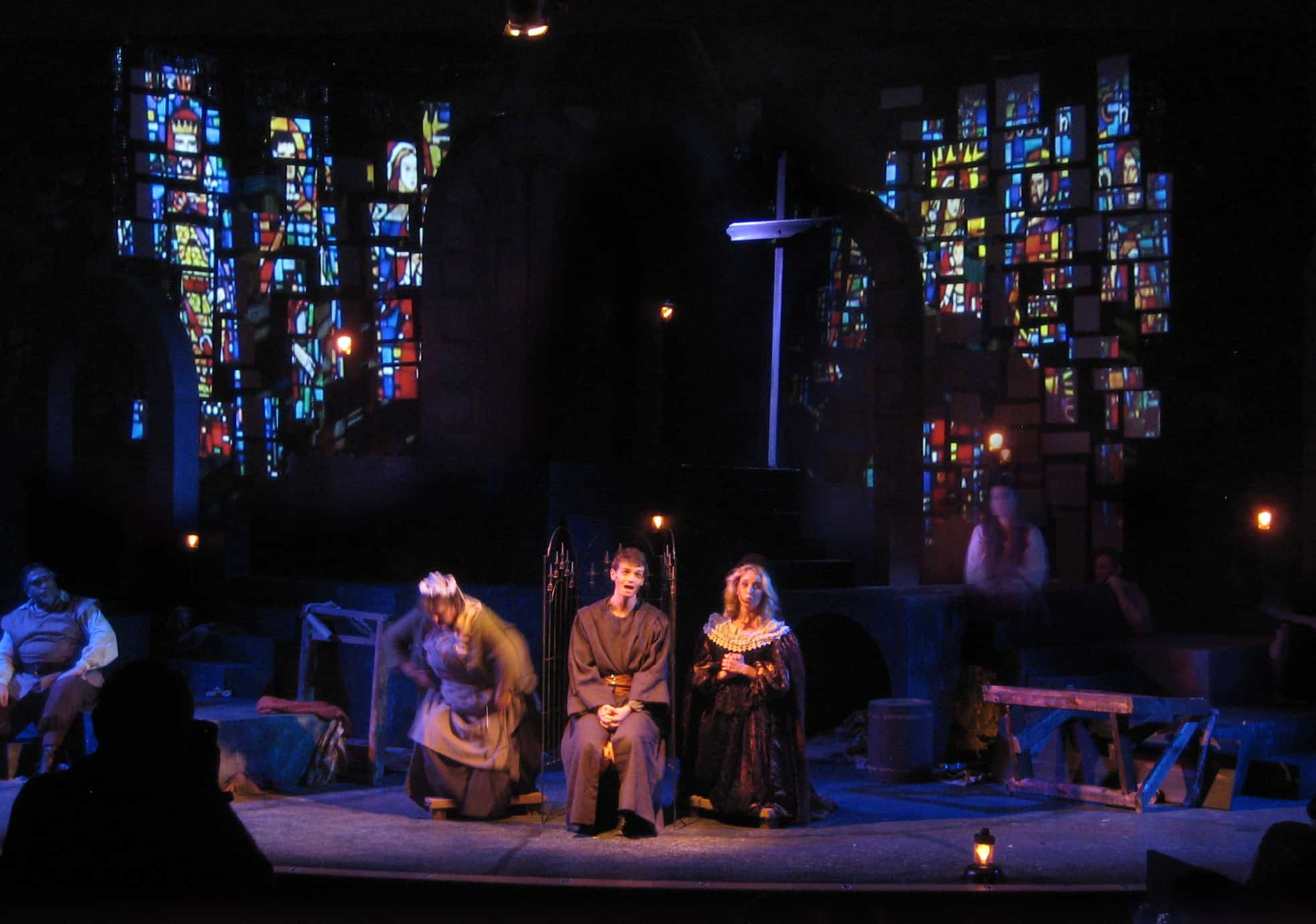 Man of La Mancha, Jean's Playhouse. Church windows are projected onto the stone bricks. A cross is erected from random sticks found in the dungeon.