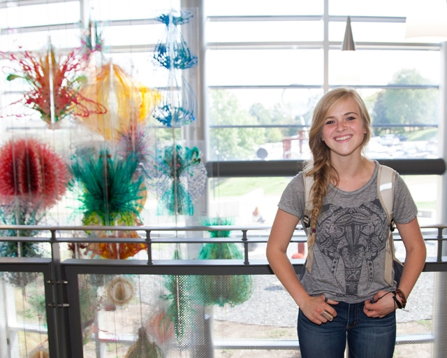 A student smiles, posing in front of the colorful sculpture in Cedar Hall