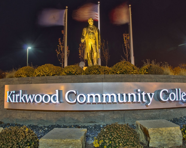 The Kirkwood main entrance lit up at night.  Flags are waving, blurry in the background.