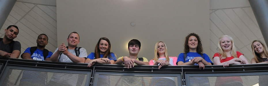 Students smile down from the 2nd floor of Cedar Hall, lined up along the railing.