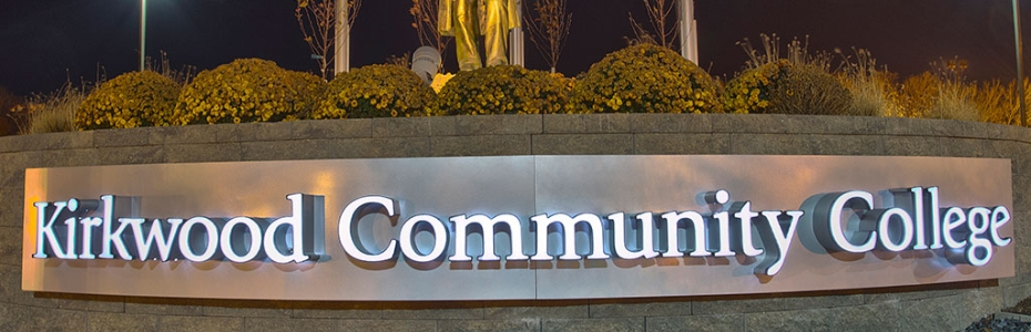 The Kirkwood Community College main entrance nameplate, lit up at night