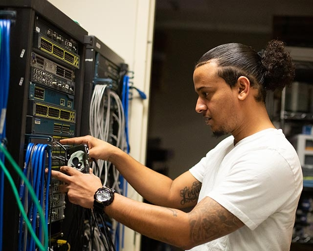 IT student working on networking equipment.