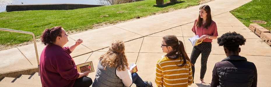 Students talking with a teacher outside on some steps