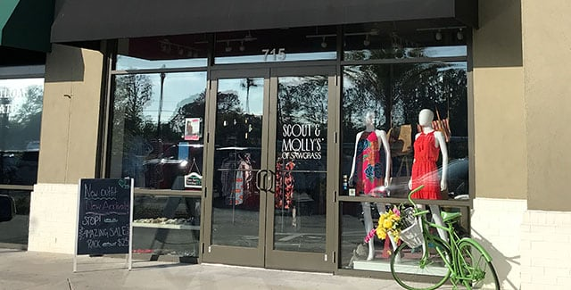 glass front doors at scout and mollys boutique of sawgrass with models in window display wearing red dresses