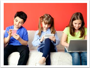 children sitting on a couch with a smartphone, tablet, and laptop