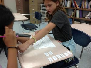 Students work collaboratively on an activity involving greatest common factor and least common multiple