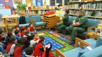 Agent Arias and Agent Acosta reading to Pre-K students at Perez Elementary