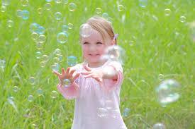 Little girl playing with bubbles.