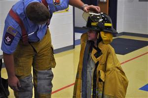 Copperas Cove firefighter helps student try on helmet during career day.