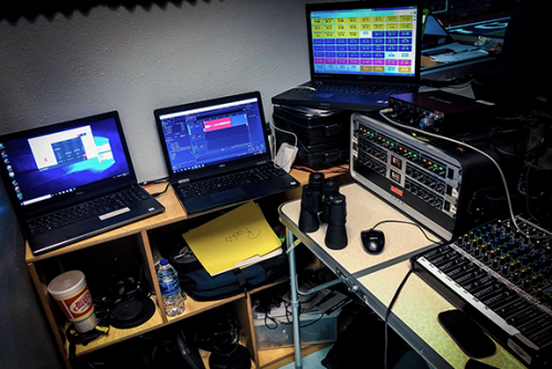 Bulldawg Radio Production Nook showing 3 laptops, Mackie ProFX 12, Behringer PreAmps and Compressor, and FocusRite USB Interface.