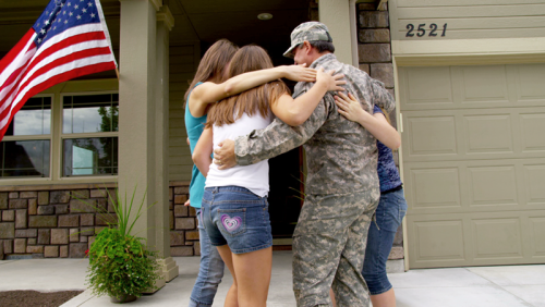 A soldier embraces his family outside of their home.