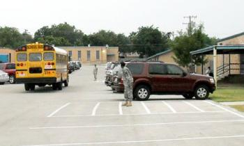 Solders welcome students to school in the bus loop.