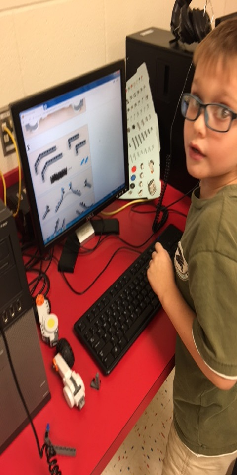 A third grade student is learning to create and program his robot during an after school club.