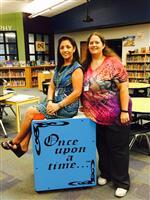 House Creek Librarians Roseanne Dietze and Sabrina Rivera Pose on a Shelving Cart.