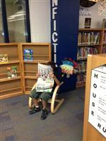 Student reading the library rocking chair.