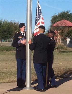 Our adopted unit wearing dress blues and raising the colors at our school flagpole.