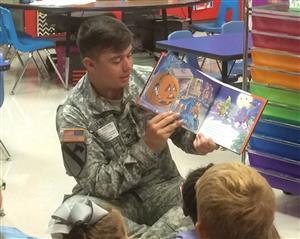 A member of our adopted unit in fatigues sits on the floor and reads to our students.