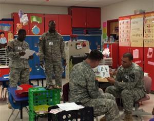 Members of our adopted unit in fatigues  read to our students.