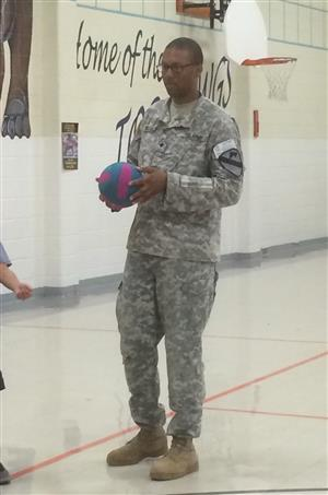 A member of our adopted unit in fatigues hold a basketball in the gym.
