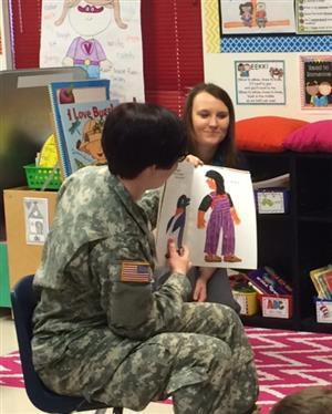 A member of our adopted unit in fatigues reads to our students.