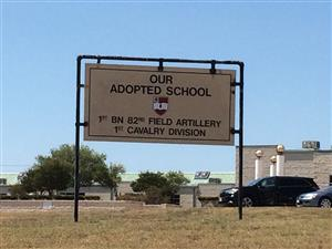 Sign in front of the school which reads: Our Adopted School 1st BN 82nd Field Artillery 1st Cavalry Division