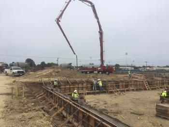 See attached photos of:  Steel is in place on grade beams in the new locker room/storm shelter area. Grade beam concrete pour from pump truck.